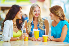 Friendly talk. Portrait of three happy girls chatting while having drink after shopping Royalty Free Stock Image