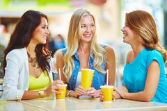 Friendly talk. Portrait of three happy girls having drink while discussing their shopping Royalty Free Stock Photo
