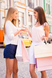 Friendly talk. Side view of two attractive young women talking while carrying shopping bags and standing outdoors Stock Photography