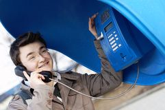 Friendly talk on telephone. Young smiling man talking on telephone Stock Photo