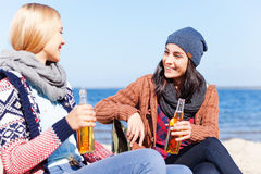 Friendly talk. Two beautiful young women drinking beer and talking to each other while sitting on the beach together Royalty Free Stock Photos