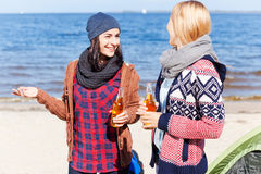 Friendly talk. Two beautiful young women drinking beer and talking to each other while standing near their tent on the riverbank Royalty Free Stock Photo