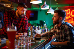 Friendly talk. Young barman and client talking in bar Royalty Free Stock Photo