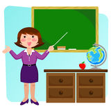 Friendly teacher. Happy teacher standing next to her desk and pointing at the blackboard Royalty Free Stock Photos