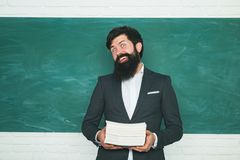 Friendly teacher in classroom near blackboard desk. Teachers challenges and inspires. Student preparing for test or exam. Back to school and happy time stock images