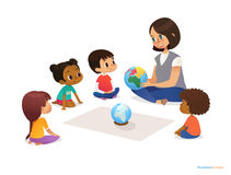 Friendly teacher demonstrates globe to children and tells them about continents. Woman teaches kids using Montessori
