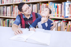 Friendly teacher teaching student in library Stock Images