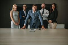 Friendly team of business professionals in boardroom. Corporate business group looking at camera and smiling in conference room Royalty Free Stock Image