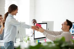 Friendly team congratulating colleague giving present gift, happ royalty free stock photo