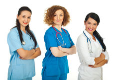 Friendly team of doctors women. Friendly team of three doctor women in different uniforms standing in semi profile in a row with hands crossed isolated on white royalty free stock images