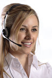 Friendly technical phone customer support. Young blonde lady with headset, white background and smile performing customer support Royalty Free Stock Images