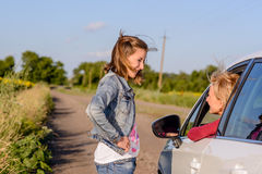 Friendly teenage girl talking with a female driver Stock Photo