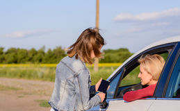 Friendly teenage girl talking with a female driver Stock Photos