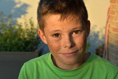 Friendly teenager boy. Portrait of a friendly teenager boy with a lot of freckles royalty free stock image