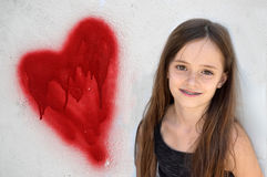 Friendly teenager girl with dental braces. Standing at a wall with graffiti heart Royalty Free Stock Image