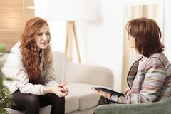 Friendly therapist supporting red-haired woman. Friendly therapist supporting red-haired women on how to manage health and life goals royalty free stock images