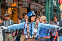 Friendly traffic warden on duty. `Gion` district, Kyoto, Japan – October 23, 2016: Between 'Hanamikoji Dori' and `Shijo Dori` junction, a female traffic Royalty Free Stock Images