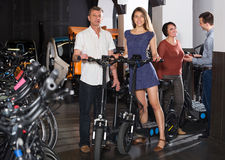 Friendly two couples hiring bicycles. Friendly happy young and elderly couples hiring bicycles ot rental store Royalty Free Stock Images