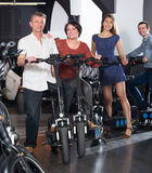 Friendly two couples hiring bicycles. Friendly smiling young and mature couples hiring bicycles ot rental store Royalty Free Stock Images