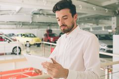 Friendly vehicle salesman presenting new cars at showroom. Photo of young male consultant showing new car in auto show. Concept for car rental stock images
