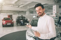 Friendly vehicle salesman presenting new cars at showroom. Photo of young male consultant showing new car in auto show. Concept for car rental royalty free stock photos