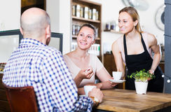 friendly waiter girl brought cup of coffee for couple of different aged people royalty free stock photography