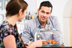 Friendly waiter offering to young female customer fresh French c Stock Photo