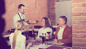 Friendly waiter placing order in front of guests. In country restaurant Royalty Free Stock Image
