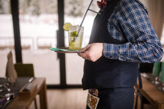 Friendly waiter serving alcoholic mohito cocktail,Refreshing lime and mint cocktail nicely decorated, Stock Image