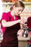 Friendly waitress making coffee Stock Photography