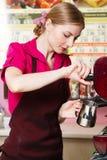 Friendly waitress making coffee Stock Photography