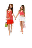 Friendly Walk. Two young women friends walking side by side, holding hands. Handbags in their opposite hands stock photo