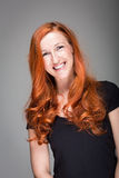 Friendly warmhearted woman. With a lovely smile and gorgeous wavy red hair, studio portrait on grey Stock Image