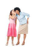 Friendly Whisper. Grandmother and her grand daughter whispering something into her ear, full length Stock Photography
