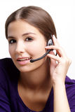 Friendly woman. A young woman with brown hair and headset Stock Images