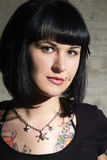 Friendly woman. Black haired woman with piercing and tattoo Stock Image