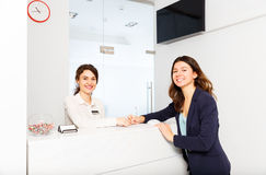 Friendly woman behind reception desk administrator with customer. Friendly young women behind the reception desk administrator with customer visitor Stock Photo
