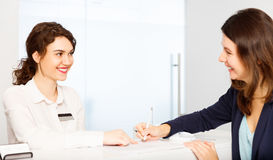 Friendly woman behind reception desk administrator with customer. Friendly young women behind the reception desk administrator with customer visitor stock photos