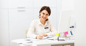 Friendly woman behind reception desk administrator. Friendly young woman behind the reception desk administrator Stock Image