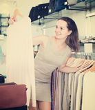 Friendly woman choosing new blouse in apparel shop Royalty Free Stock Photo
