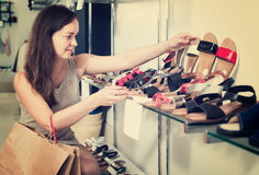 Friendly woman customer selecting shoes in footgear center. Portrait of friendly woman customer selecting shoes in footgear center Stock Photo