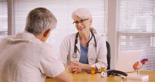 Friendly woman doctor prescribing medication to elderly patient Royalty Free Stock Photography
