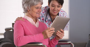 Friendly woman and Elderly patient talking with tablet Royalty Free Stock Photos