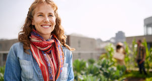 Friendly woman harvesting fresh vegetables from the rooftop greenhouse garden Royalty Free Stock Photography