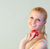 Friendly woman holding an apple. Close-up of an friendly woman holding an apple with focus on woman Royalty Free Stock Images
