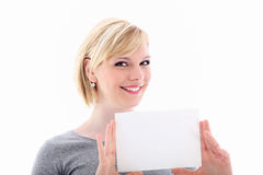 Friendly woman holding small blank sign. Friendly attractive blonde woman holding up a small blank sign for your text or advertisement isolated on white Royalty Free Stock Photos