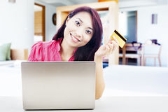 Friendly woman online shopping. Smiling young asian woman holding a credit card with laptop computer. shot at home Stock Photos