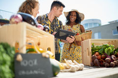 Friendly woman tending an organic vegetable stall at a farmer's market and selling fresh vegetables from the rooftop Stock Images
