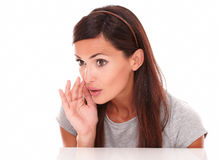 Friendly woman whispering and looking at people Stock Photos