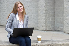 Friendly woman working on laptop outside Stock Image